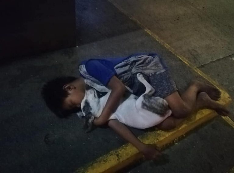 Il piccolo dorme abbracciato al cane su un marciapiede di Manila