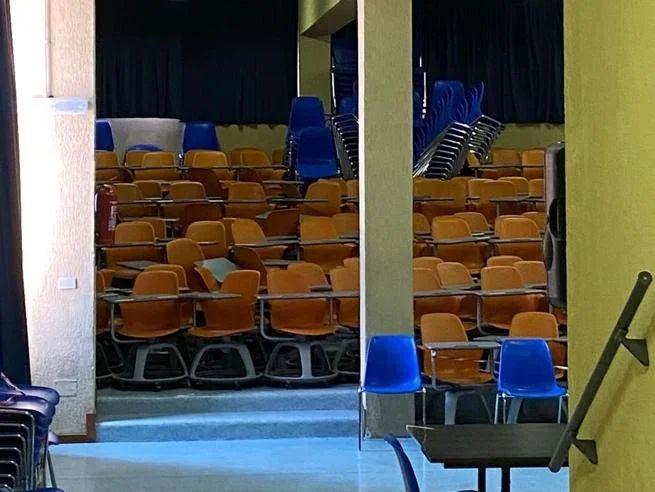 Scuola : Aula magna del Liceo Seneca piena di banchi a rotelle inutilizzati